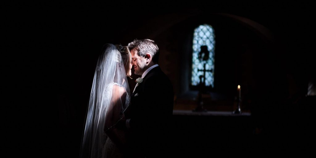 Wedding Photographers in Surrey beautiful dark image of bride and groom kissing in church in Godalming